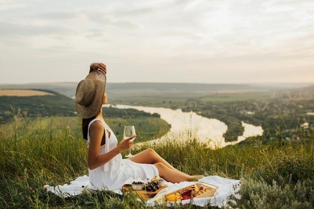 Splendida giovane ragazza bruna in un prendisole bianco e cappello di paglia che si gode un picnic in un luogo pittoresco.