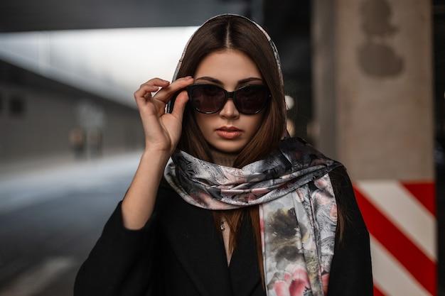Splendida giovane donna bruna in abiti eleganti raddrizza gli occhiali da sole. modello di ragazza professionale in un cappotto nero alla moda con una sciarpa di seta vintage sulla testa in posa sulla strada vicino alla strada.