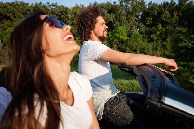 Splendida giovane donna dai capelli scuri in occhiali da sole con giovane riccio sono seduti e sorridenti in una cabriolet nera in una giornata di sole. .