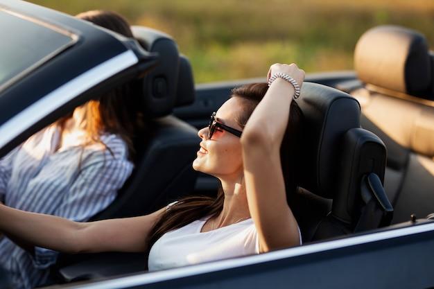 Splendida giovane donna dai capelli scuri in occhiali da sole vestita con una t-shirt bianca seduta in una cabriolet e sorridente in una giornata di sole. .