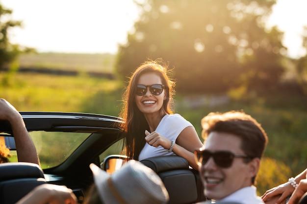Splendida giovane donna dai capelli scuri in occhiali da sole sorride e si siede con gli amici in una cabriolet nera in una giornata di sole. .