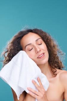 Bellissima giovane donna che gode della sensazione di morbidezza e idratazione della sua pelle mentre tocca il viso con un asciugamano di cotone dopo averlo lavato