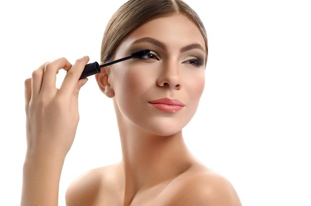 Splendida giovane femmina che tiene il pennello mascara isolato su bianco