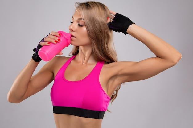 Bellissima giovane donna fitness in una maglietta sportiva brillante con acqua da bere durante un allenamento.