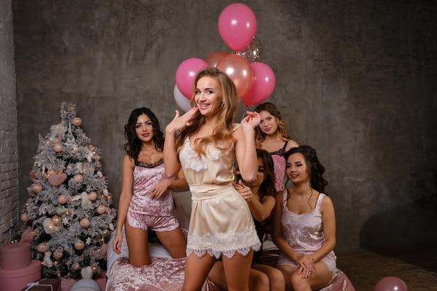 Splendide giovani donne in lingerie sexy che si godono il loro addio al nubilato, sedute sul letto, in posa e sorridenti. studio con albero di natale, decorazioni, palloncini. addio al nubilato, bellezza, moda. avvicinamento.