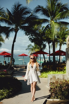 Splendida giovane donna in bikini in posa sotto le palme nel territorio del lussuoso resort sul...
