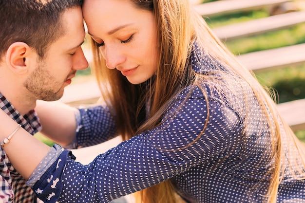 Giovane donna splendida che abbraccia dolcemente il suo uomo con gli occhi chiusi