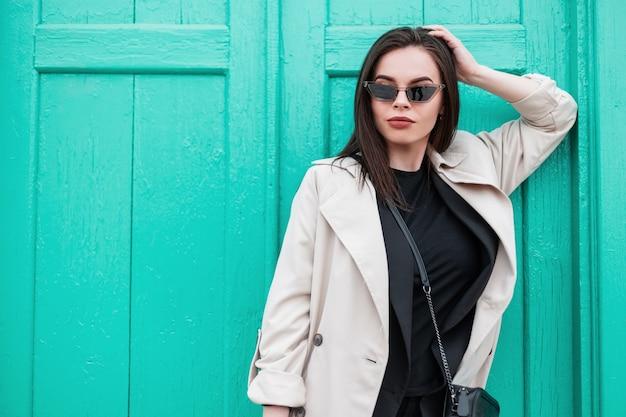 Splendida giovane donna in occhiali da sole retrò alla moda in t-shirt nera alla moda in elegante trench primaverile è riposa vicino alla porta turchese in legno brillante vintage sulla strada. modello di moda ragazza urbana all'aperto.