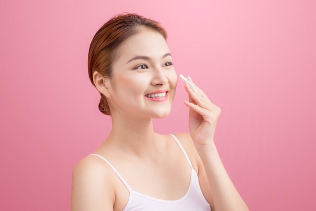 Splendida giovane donna che tiene un batuffolo di cotone e sorride nel prendersi cura del suo viso per una cura della pelle fresca e sana su sfondo rosa