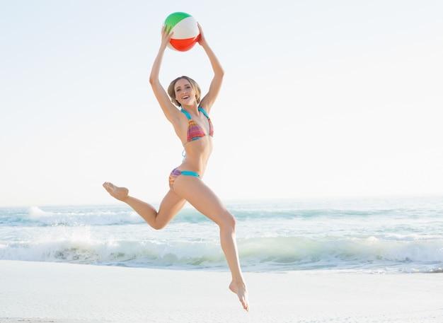 Giovane donna splendida che salta sulla spiaggia che tiene un beach ball