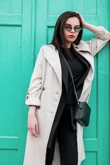 Splendida giovane donna in occhiali da sole in abito casual alla moda. ragazza sexy in trench in blazer vintage in elegante t-shirt nera vicino alla porta turchese in legno brillante in città. abbigliamento alla moda per le donne.