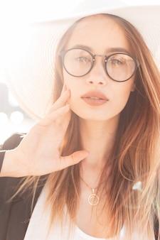 Splendida giovane donna con belle labbra in occhiali alla moda in cappello elegante elegante bianco paglia in giacca nera alla moda in posa in pieno sole. affascinante bella ragazza al tramonto. ritratto di moda.