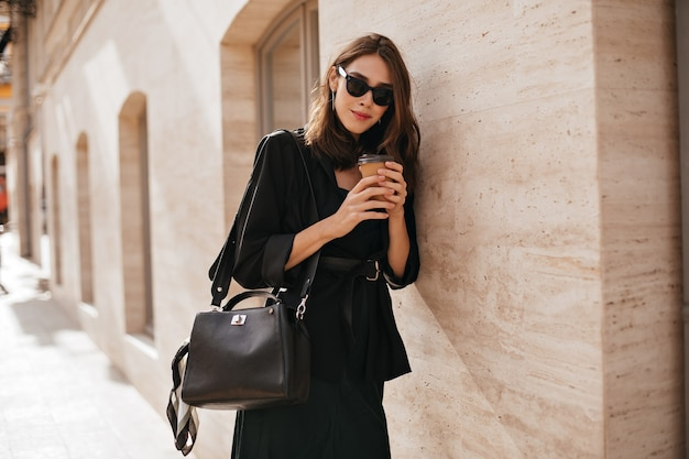 Splendida giovane donna con acconciatura ondulata bruna, occhiali da sole, cappotto nero e borsa che cammina nella città diurna e posa contro il muro beige