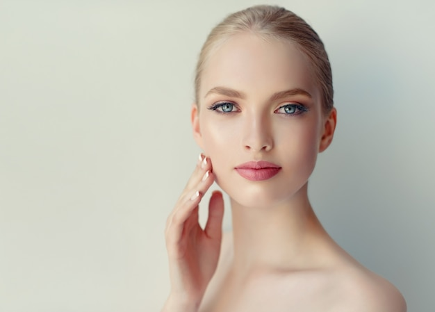 Bellissima, giovane, donna con pelle fresca e pulita, trucco delicato e rossetto rosa sulle labbra sta toccando il viso.