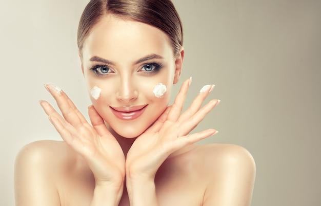 Bellissima, giovane donna con macchie di crema cosmetica sulla pelle ben curata