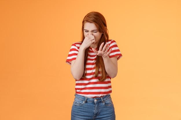Accidenti, puzza riluttante disgustata donna rossa alza la mano blocca gesto antipatia chiudi il naso rabbrividire f...