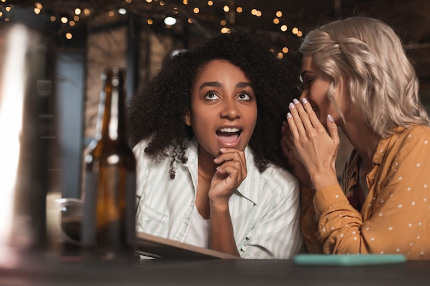 Amante del pettegolezzo. donna abbastanza riccia seduta al bancone del bar accanto alla sua amica che la ascolta sussurrare nell'orecchio e raccontare pettegolezzi