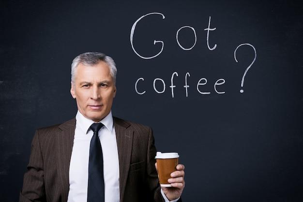 Hai il caffè? fiducioso uomo anziano in abiti da cerimonia che tiene una tazza di caffè e guarda la telecamera mentre si trova contro la lavagna con un disegno a gesso su di essa