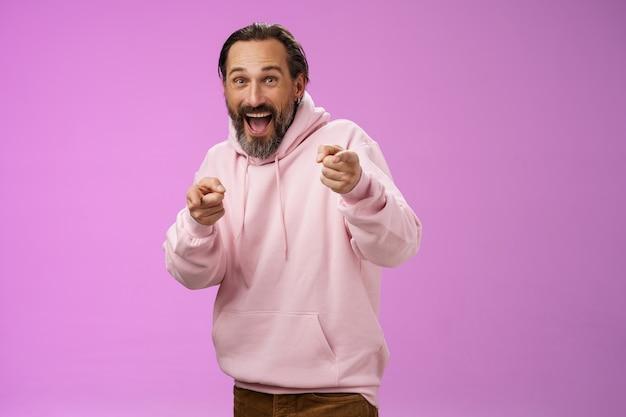 Gotcha. ritratto spensierato divertente divertente adulto eccitato uomo barbuto che salta scherzo amico divertendosi ridendo felicemente indicando le dita indice della fotocamera saluto raccogliendo, sfondo viola.