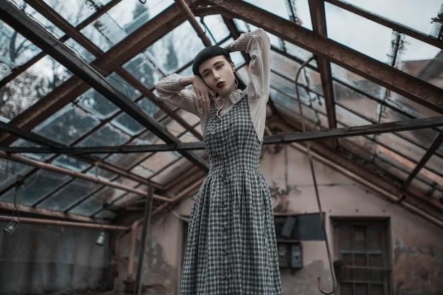 Modello gotico bruna in abito. moda vittoriana. modello gotico su sfondo grunge. misteriosa donna bruna con botto. modello in abito su sfondo abbandonato. vestiti di moda. vampiro misterioso