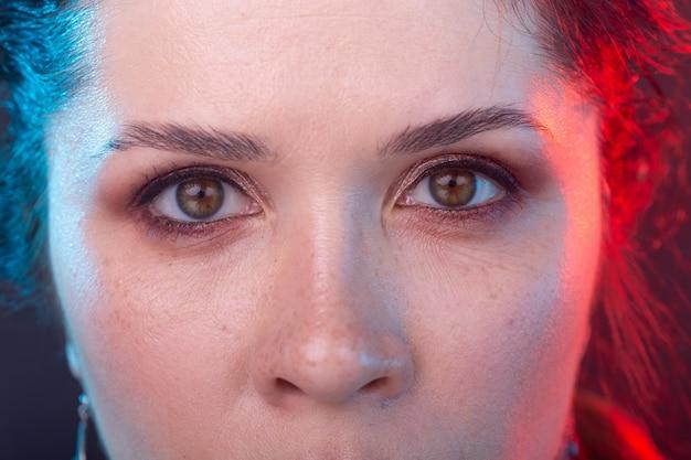 Concetto gotico, halloween e persone - primo piano della donna affascinante degli occhi nel trucco gotico