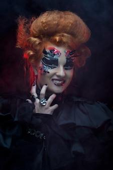 Strega gotica dai capelli rossi. donna oscura. trucco artistico. foto di halloween.