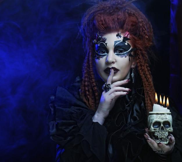 Donna gotica dai capelli rossi vampiro con teschio.