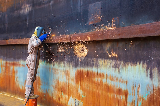 Sgorbiatura saldatura scintilla fuoco saldatore industriale indossare maschera protettiva di sicurezza costruzione riparazione serbatoio olio saldatura per nuova parte in specifiche confinate