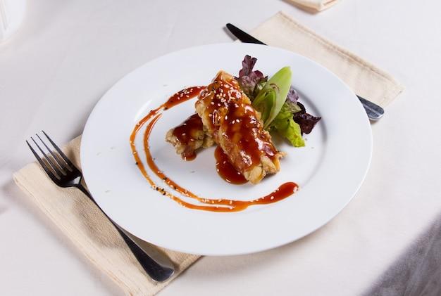 Gourmet appetitoso impertinente piatto principale di carne fritta su piatto rotondo bianco, cenare in tavolo bianco.