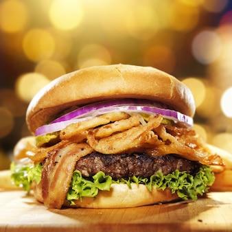 Hamburger gourmet di pancetta con sfondo dorato e composizione nello spazio della copia.