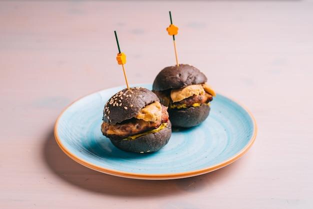 Mini hamburger di manzo gourmet con pane nero su un piatto