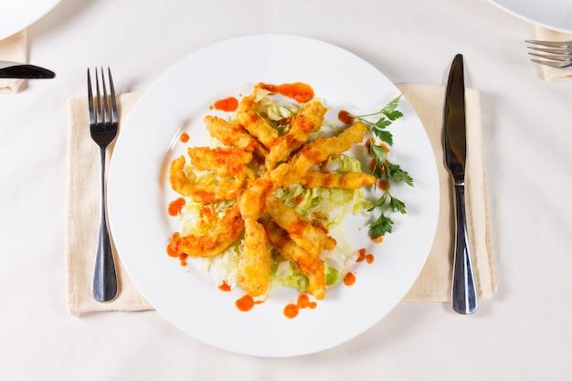 Piatto di carne fritta croccante gourmet sul piatto rotondo bianco, cenare sul tavolo bianco con utensili.