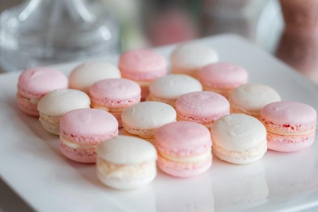 Dessert francese gourmet. macarons delicati. macarons rosa e bianchi. dessert di nozze su uno sfondo di specchio