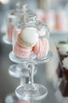 Amaretti gourmet in un vaso di vetro con un coperchio su uno sfondo a specchio. macarons alla vaniglia e alla fragola. dessert francese.