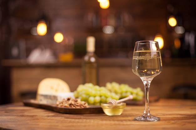 Serata gourmet in un ristorante vintage con degustazione di vini bianchi e formaggi. uva fresca. bicchiere di vino. noci gustose.