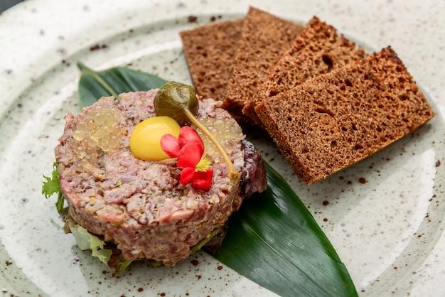 Tartare gourmet crudo di filetto di manzo con il giallo dell'uovo alla griglia e baguette come primo piano su un piatto dal design moderno