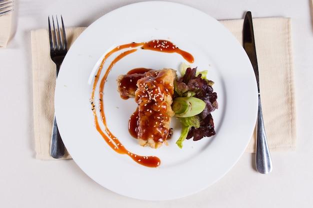Gourmet gustoso piatto principale su piatto rotondo bianco con utensili sui lati servito su un tavolo bianco per gli ospiti del ristorante.