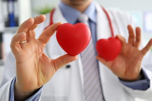 Gp che mostra due cuori rossi in primo piano della fotocamera. la formazione di cpr per gli studenti cardio-terapeuti salva la vita del medico di famiglia rende il concetto di aritmia di misurazione della frequenza cardiaca fisica cardiaca