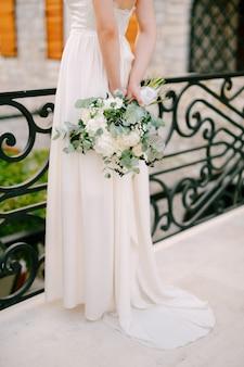 Una graziosa sposa si trova su un ponte in ferro battuto nella città vecchia di budva e tiene dietro di sé un bouquet