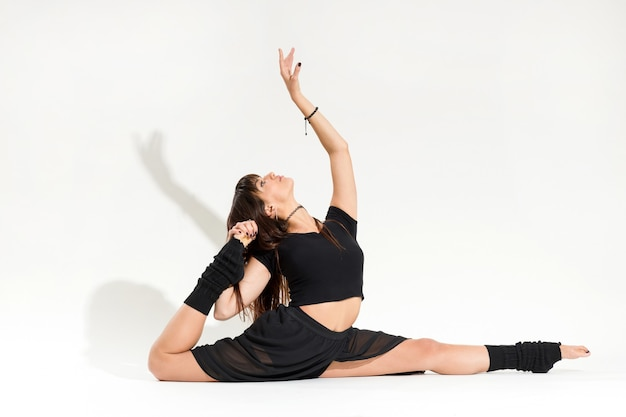 Graziosa e flessibile giovane ballerina che esegue un esercizio di divisione anteriore in una vista a livello del pavimento isolata su uno sfondo bianco per studio con ombra e copyspace
