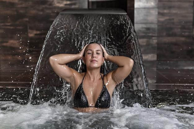 Donna graziosa in bikini che bagna sotto il getto della cascata