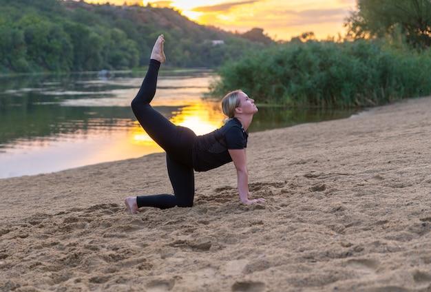 Donna graziosa che colpisce una posa di yoga al tramonto