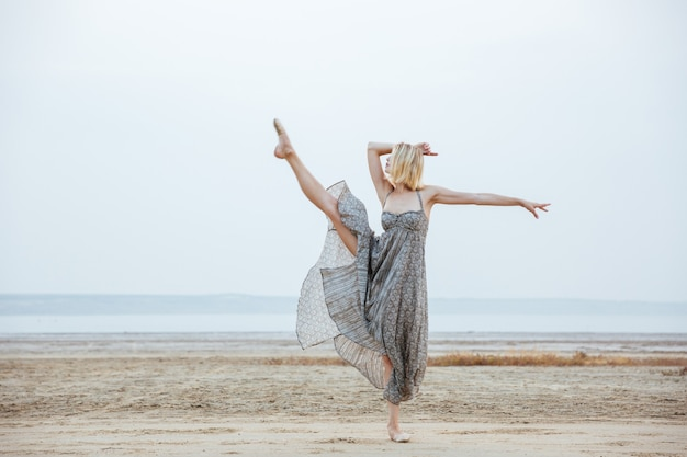 Ballerina graziosa della giovane donna in bello vestito che balla sulla spiaggia