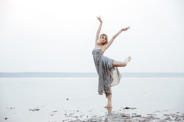 Graziosa giovane donna in abito lungo che balla all'aperto nel lago