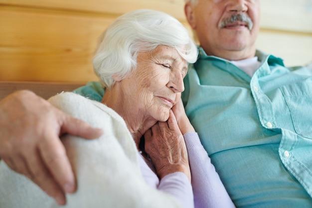 Graziosa nonna con i capelli bianchi che fa un sonnellino sulla spalla del coniuge mentre entrambi si rilassano sul divano davanti al televisore