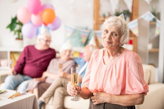 Graziosa femmina senior con flute di champagne che tostano per il compleanno a casa festa con gli amici