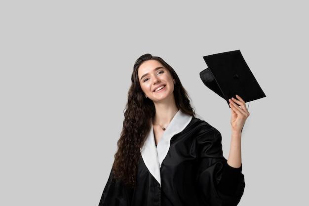 Ragazza laureata con master in abito da laurea nero e berretto. apprendimento a distanza online. studia a casa. laurea dal college.
