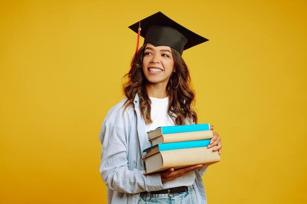 Donna laureata in un cappello di laurea in testa, con libri su giallo.