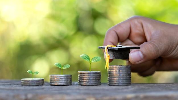 Cappelli dei laureati sulle monete e sulle mani delle persone, comprese le piante che crescono sulla moneta.
