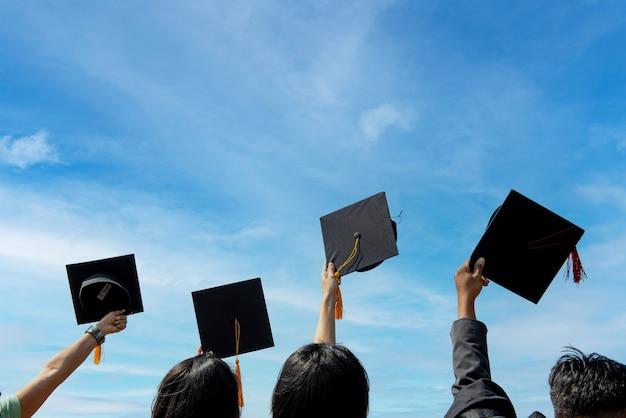 Laureati che lanciano cappelli da laurea in cielo